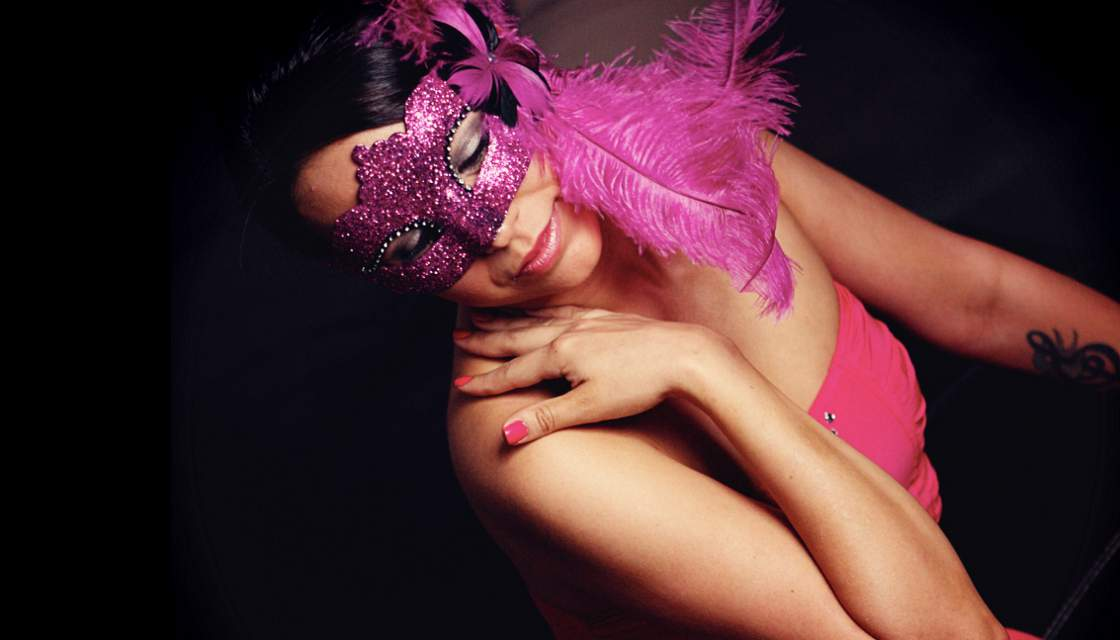 Girl wearing pink feathered mask and dress to Penthouse party