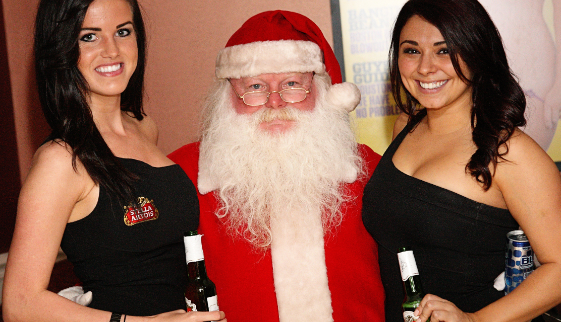 Penthouse pets posing for a photo at the strip club with Santa Claus