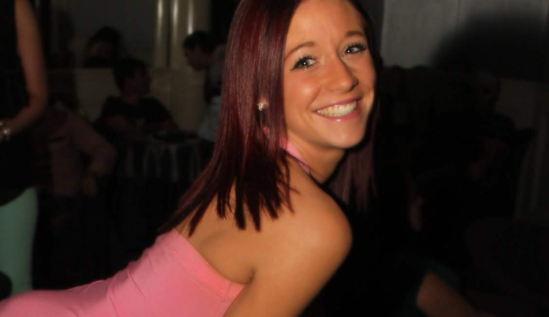 Smiling brunette in a pink shirt at the Baton Rouge strip club image - The Penthouse Club