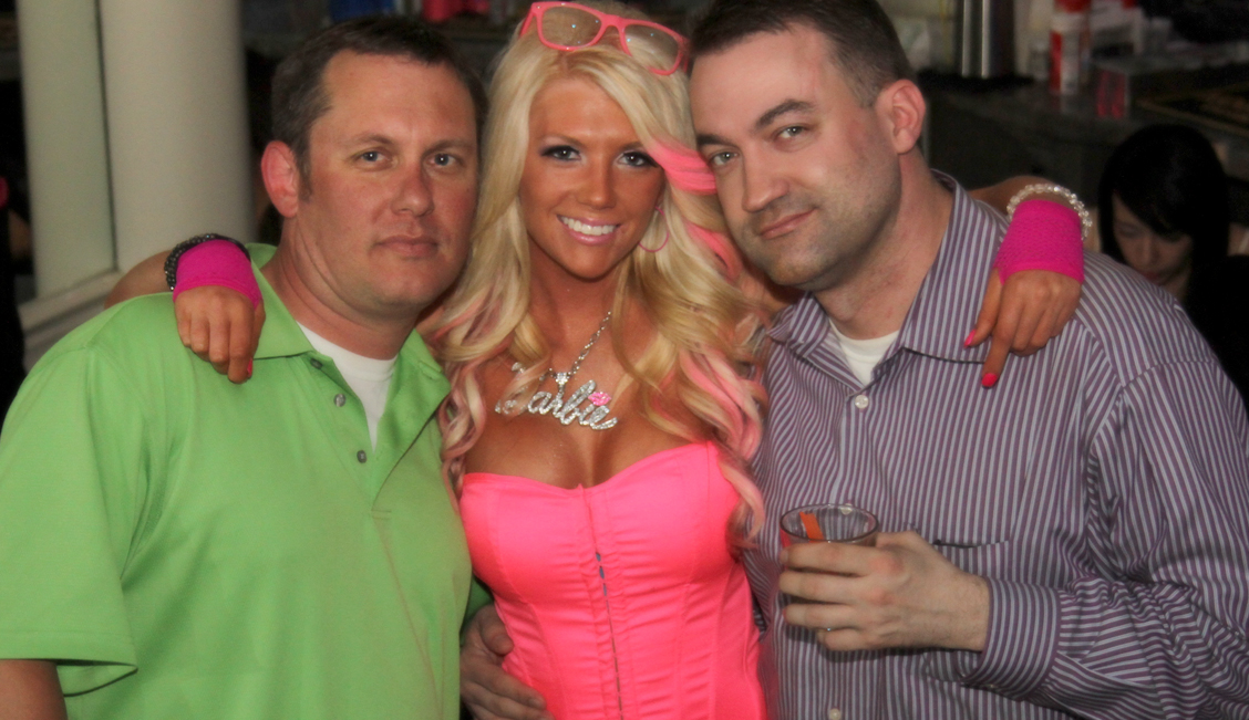Barbie pink blonde posing with two happy men in the Baton Rouge strip club - The Penthouse Club